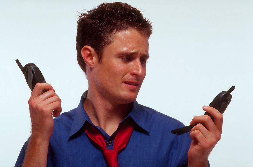 A stressed, young profssional man represents The Cellular Age with one phone in each hand.