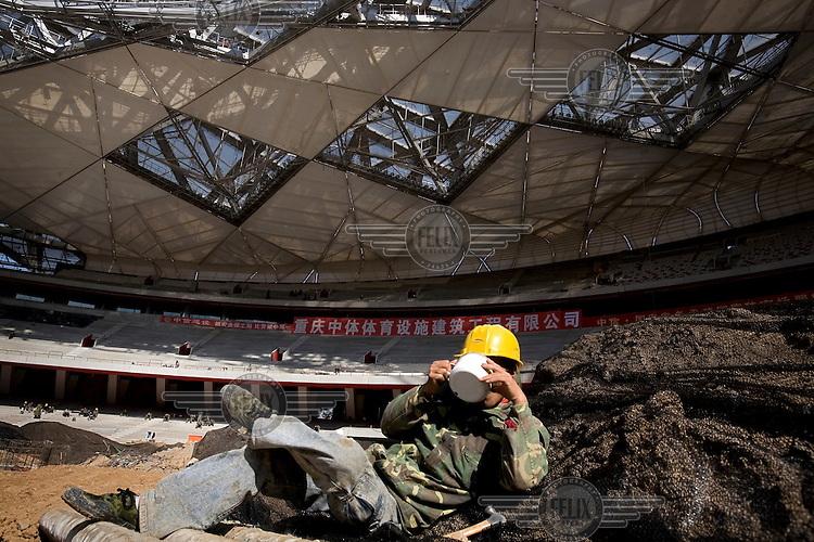 """A construction worker in Beijing takes a break inside the """"Bird's Nest"""" National Stadium, which will be unveiled for the 2008 Olympic Games."""