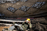 "A construction worker in Beijing takes a break inside the ""Bird's Nest"" National Stadium, which will be unveiled for the 2008 Olympic Games."