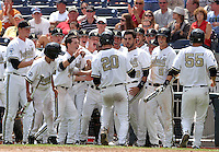 Vanderbilt's Connor Harrell (20) is greeted by teammates after hitting the first home run in the new TD Ameritrade Park Omaha. Vanderbilt beat UNC 7-3 to open the 2011 College World Series in Omaha, Neb. (Photo by Michelle Bishop)..
