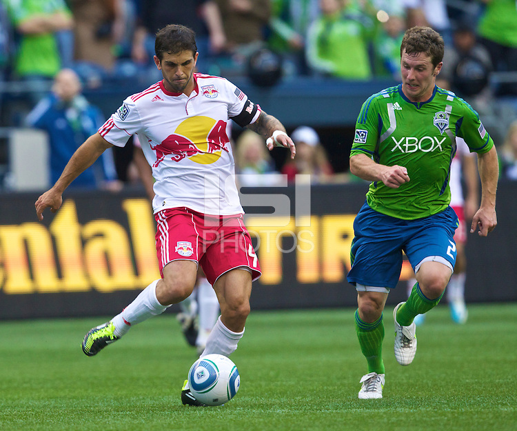 New York Red Bulls defender Carlos Mendes dribbles the ball up field against Seattle Sounders FC forward Mike Fucito  during play against at Qwest Field in Seattle Saturday June 23, 2011. The Sounders won the game 4-2.