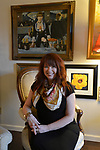 "Sandy Stolberg relaxes in the living room of her condo. On the wall behind her is a print of Edouard Manet's painting, ""A Bar At the Folies-Bergere"". Photo taken on January 8, 2019 for ""At Home"" feature on Sandy Stolberg,  who uses dollar store finds as part of the decorations in her Belleville, IL condo.<br /> Photo by Tim Vizer"