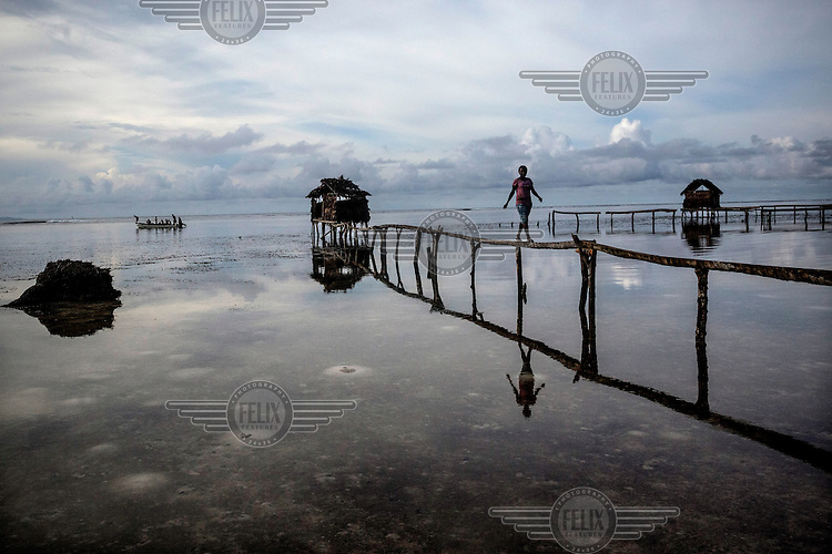 A woman returns from the shared toilet at the end of a long jetty in Mbunai village.