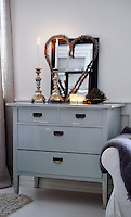 A restored vintage chest of drawers helps to divide the living room and dining area