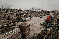 A woman walks in the devastated by fire area of Breezy Point, NY. Hundred and one houses burned in the village when Hurricane Sandy hit the area.