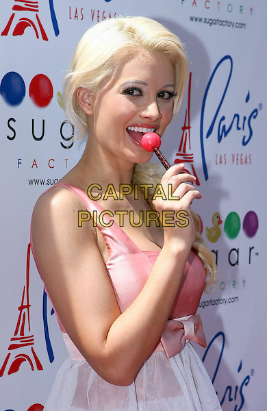 "HOLLY MADISON .debuts signature ""Vegas"" Pops at Sugar Factory at Paris Resort Hotel and Casino and then makes an appearance at the Sugar Factory at the Planet Hollywood Resort Hotel and Casino, Las Vegas, Nevada, USA, 20th July 2010..half length pink bow dress white tiered ruffle lollypop lolly peach coral .CAP/ADM/MJT.© MJT/AdMedia/Capital Pictures."