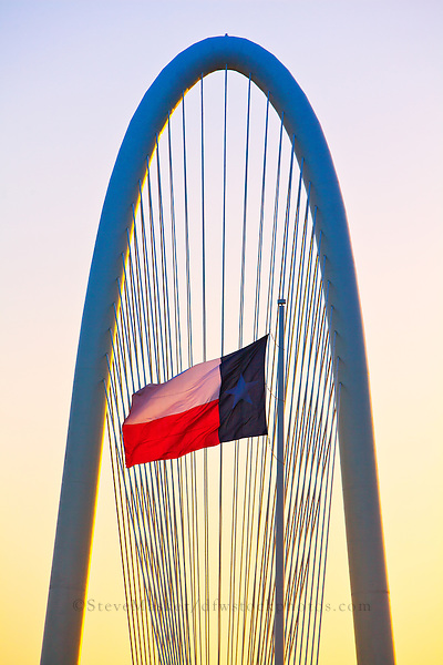 """Margaret Hunt Hill Bridge at Sunrise"" – Standing in front of The Margaret Hunt Hill Bridge, the Lone Star Flag flutters in the wind as the morning sun breaks the horizon. Positioned across the Trinity River, The Margaret Hunt Hill Bridge – positioned West of downtown Dallas – was designed by Spanish architect Santiago Calatrava and opened in March 2012."