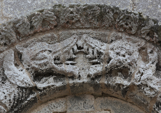Carved heads of 2 dragons with open mouths on the North portal of the Church of St Radegonde, built 1094 in Romanesque style, in Talmont sur Gironde, Poitou-Charentes, France. The church overlooks the Gironde Estuary and is on the Via Turonensis pilgrimage route on the way to Santiago de Compostela. Picture by Manuel Cohen