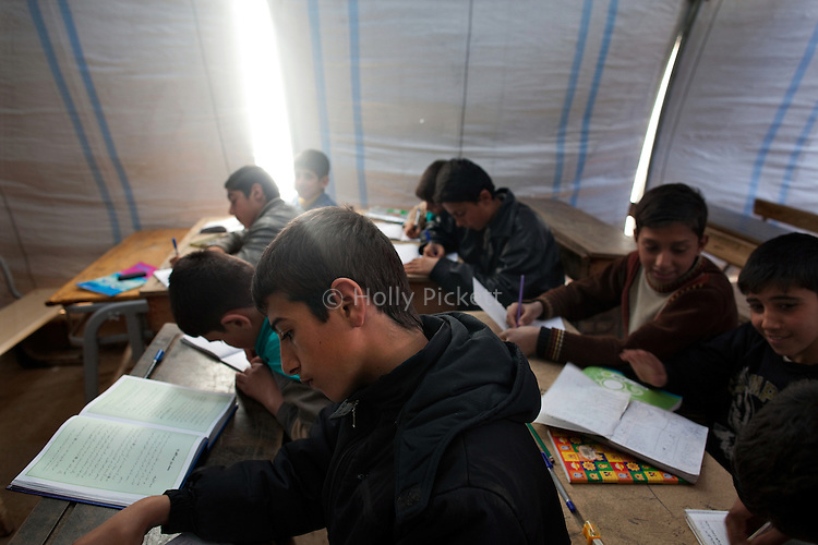 "Eighth-grade boys attend religion class at the school in Azaz Camp, just inside the Syrian border with Turkey, Feb. 26, 2013. A private charity donated the tents for the school, which has around 800 students between the ages of 6 and 16. Desks and other materials were salvaged from schools in Azaz village a few kilometers away. The school opened two months ago, and because there are so many children, they attend either a morning or an afternoon session, learning math, Arabic, English, and religion. Almost all of the teachers and staff are refugees and reside in the camp. The children come to school with special challenges--they may have psychological distress because of traumatic events or health problems due to poor living conditions in the camp, and some have not been in school for a long time and have to catch up to their grade level. ""We try everything to make them happy,"" said a teacher, Abdul Razaq. According to administrators, this camp holds roughly 9,000 to 10,000 internally displaced persons (IDP's). Two meals per day are provided by a Turkish humanitarian organization, and Qatar Red Crescent provided tents. There is very little electricity, and no running water. There is also a refugee camp on the Turkish side of the border, but it is full. The UN Refugee Agency has reported a sharp increase in refugees fleeing Syria for neighboring countries in the first months of 2013."