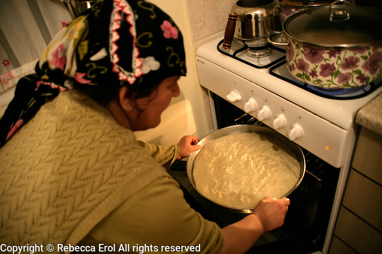 Turkish woman putting cornflour bread (misir ekmek) into the oven, Turkey