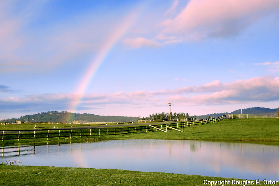 A morning rainbow hovers over a rain swollen San Juan Valley farm pond.  Along  San Juan Valley Road on San Juan Island, near the town of Friday Harbor.  San Juan Islands group, Salish Sea, Washington State, USA