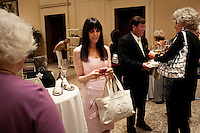 "Newport, California, July 22, 2011 - Contributor Julie Spira, center, checks her phone at The Divorcee Sale at the Pelican Hill Resort in Orange County. Organized by Jill Alexander, the sale offers luxury items most of which from uber-rich divorcees looking to unload their proverbial baggage. The event also donates 25 percent of its profits to breast cancer research...Alexander, who has actually never been married, started The Divorcee Sale this past spring after noticing a trend amongst her friends and colleagues going through divorces. ""Many women have an attachment to these things and they just want to move on,"" says Alexander. She added that the consignment shops were full and not really offering much in the way of sympathy in the situation. Alexander is different in that she visits the home of the divorcees, often with cakes and tissues, and acts as both a consignor and a confidant. ."