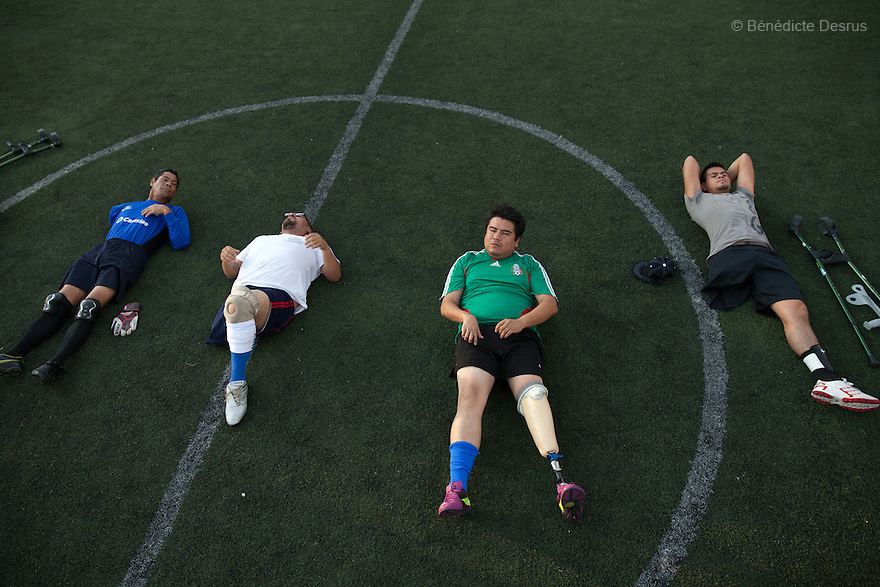 """Players from Guerreros Aztecas do sit-ups as part of their training in Mexico City, Mexico on June 12, 2014. Guerreros Aztecas (""""Aztec Warriors"""") is Mexico City's first amputee football team. Founded in July 2013 by five volunteers, they now have 23 players, seven of them have made the national team's shortlist to represent Mexico at this year's Amputee Soccer World Cup in Sinaloathis December.The team trains twice a week for weekend games with other teams. No prostheses are used, so field players missing a lower extremity can only play using crutches. Those missing an upper extremity play as goalkeepers. The teams play six per side with unlimited substitutions. Each half lasts 25 minutes. The causes of the amputations range from accidents to medical interventions – none of which have stopped the Guerreros Aztecas from continuing to play. The players' age, backgrounds and professions cover the full sweep of Mexican society, and they are united by the will to keep their heads held high in a country where discrimination against the disabled remains widespread.(Photo byBénédicte Desrus)"""