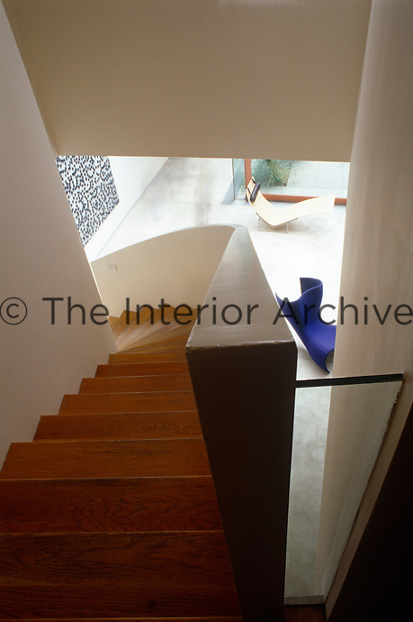 View looking down the steep curved flight of wooden steps encased in white concrete which leads to the living area