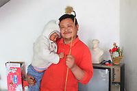 Dans la maison de monsieur Junrong, cet ancien militaire revenu au pays pose avec son jeune fils, sa canne à pollen. Derrière lui, un téléviseur et une statue de Mao datant de la révolution culturelle.///In Mister Junrong's house: this former soldier, come back to his native land, poses with his young son and pollen cane. Behind him, a television and a statue of Mao date from the Cultural Revolution.
