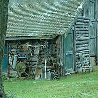 A collection of tools is stacked against the wall of this log cabin