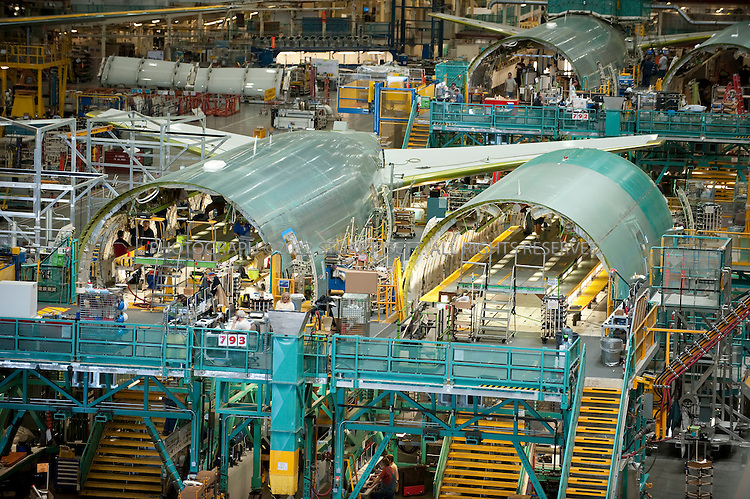 """4/30/2009--Everett, WA, USA..Boeing 777s under construction at the Everett, WASH. factory. The Boeing 777 is a long-range, wide-body twin-engine airliner manufactured by Boeing Commercial Airplanes. The world's largest twinjet and commonly referred to as the """"Triple Seven"""", the aircraft can carry between 283 and 368 passengers in a three-class configuration, and has a range from 5,235 to 9,380 nautical miles (9,695 to 17,372 km). Distinguishing features of the 777 include the largest diameter turbofan engines of any aircraft, six wheels on each main landing gear, its circular fuselage cross-section and the blade-like end to the tail cone..©2009 Stuart Isett. All rights reserved."""