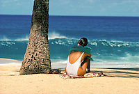 Woman watching waves near palm tree. Waimea beach park, north shore, Oahu.