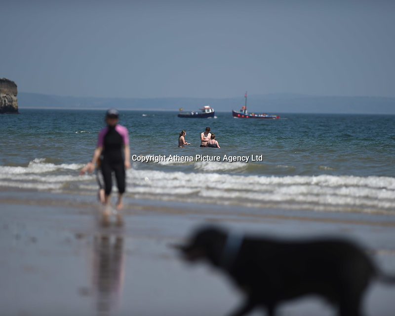 Thursday 25 May 2017<br /> Pictured: People enjoy taking a dip as boats pass by <br /> Re: People enjoy the warm sunshine in Tenby, , West Wales. Temperatures today are expected to reach the high 20s Centigrade in many parts of the UK, making it one of  warmest days of the year so far