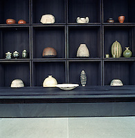 A collection of ceramics is displayed in specially constructed open shelving designed in large square modules
