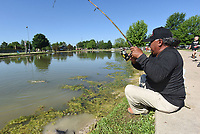 NWA Democrat-Gazette/FLIP PUTTHOFF <br />Felix Soto reels in a channel catfish May 26 2018 at Veteran's Park in Rogers during the Care Community Center family fishing derby. Worms or nightcrawlers are excellent bait for channel catfish. Flathead catfish prefer sunfish or large minnows.
