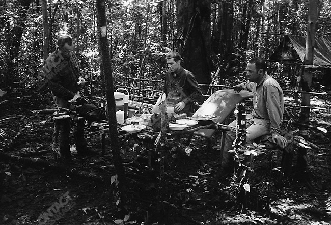 Regrouping at their base camp after their initial encounter with native tribesmen. From left to right, Austrian traveler Robert Frediny, tour guide Kelly Woolford and writer Michael Behar, disscuss what to do next. West Papua, Indonesia, September 2004.