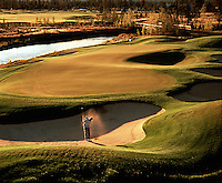 Overview of golfer hitting out of sand on the 8th hole on the Crosswater Course. Sunriver, Oregon.
