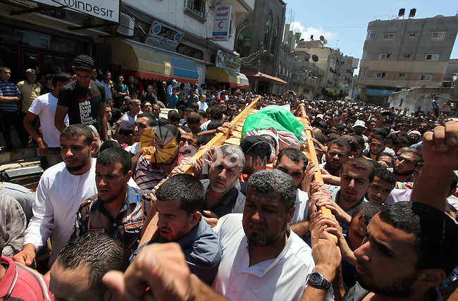 Palestinians carry the bodies of Nidal Badran and Mouath Zaied, who medics said were killed after an Israeli airstrike on a al-Qassam mosque, during their funeral in Nuseirat refugee camp in the central Gaza Strip on August 9, 2014. Israel launched more than 20 aerial attacks in Gaza early on Saturday and militants fired several rockets at Israel in a second day of violence since a failure to extend an Egyptian-mediated truce that halted a monthlong war earlier this week. The Israeli military said that since midnight it had attacked more than 20 sites in the coastal enclave where Hamas Islamists are dominant, without specifying the targets. Medical officials in Gaza said two Palestinians were killed when their motorcycle was bombed and the bodies of three others were found beneath the rubble of one of three bombed mosques. The air strikes which lasted through the night also bombed three houses, and fighter planes also strafed open areas, medical officials said. Photo by Ashraf Amra