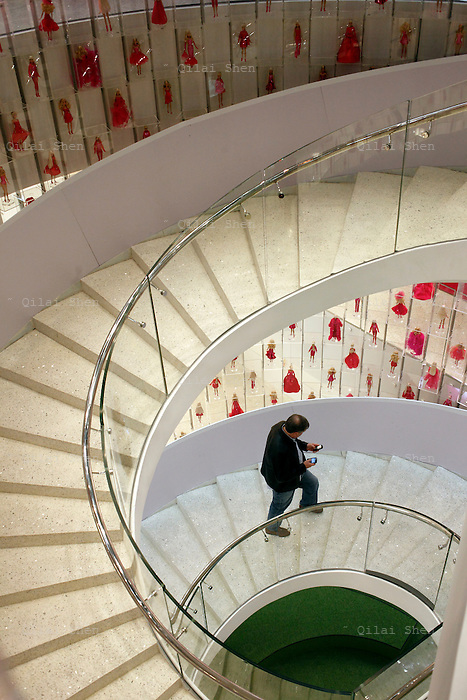 A visitor walks up a spiral staircase surrounded by Babie dolls during the Media Sneak Preview of the new Barbie Shanghai flagship store in Shanghai, China on 20 February 2009.  The Barbie store has become a hit in Shanghai as a place where doting mothers take their daughters, often the only child in the family, for a girls' day out.
