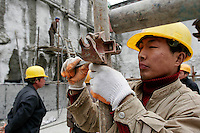 Workers erect steel scaffoldings at a construction site in Beijing, China..