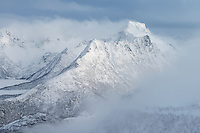 Breidtind mountain peak emerges from clouds in clearing winter storm, Austvågøy, Lofoten Islands, Norway