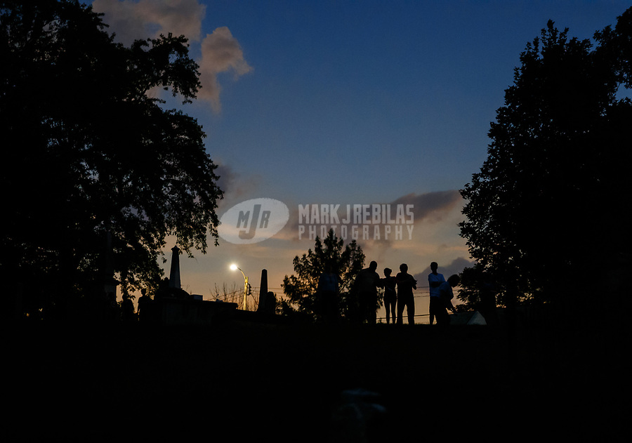 Aug 17, 2017; Sainte Genevieve, Missouri, USA;  People view a total solar eclipse during totality as viewed from a graveyard cemetery in the town of Sainte Genevieve, Missouri. A solar eclipse is caused when the moon blocks the sun and casts a shadow on the Earth. Mandatory Credit: Mark J. Rebilas