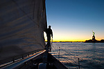 A man looking at the Statue of Liberty at sunset from a classic schooner, The Shearwater, in New York Harbor