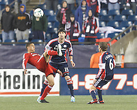 Toronto FC forward Luis Silva (11) passes the ball as New England Revolution defender Stephen McCarthy (15) defends. In a Major League Soccer (MLS) match, the New England Revolution (blue) defeated Toronto FC (red), 2-0, at Gillette Stadium on May 25, 2013.