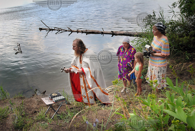 The service of baptism of 5 year old Paulina by Russian Orthodox priest Father Alexander in a lake in the countryside near Abakan.