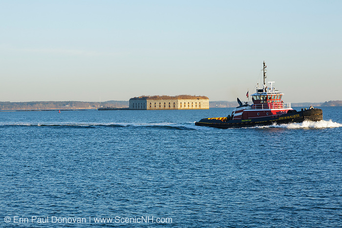 Tug boat passes by Fort Gorges in South Portland, Maine USA, which is part of the New England seacoast.