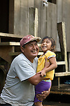 A father lifts daughter outside his home in Crique Sarco village in southern Belize.  He is the town judge handling small claims.  It is a traditional Mayan village.
