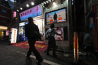 A woman watches news about Japanese hostages held by Islamic State outside a night station information shop in Kabukicho red-light district, Shinjuku, Tokyo, Japan. Friday January 23rd 2015. Hostages, Kenji Goto and Haruna Yukawa are threatened with execution unless a $200 million ransom is paid.