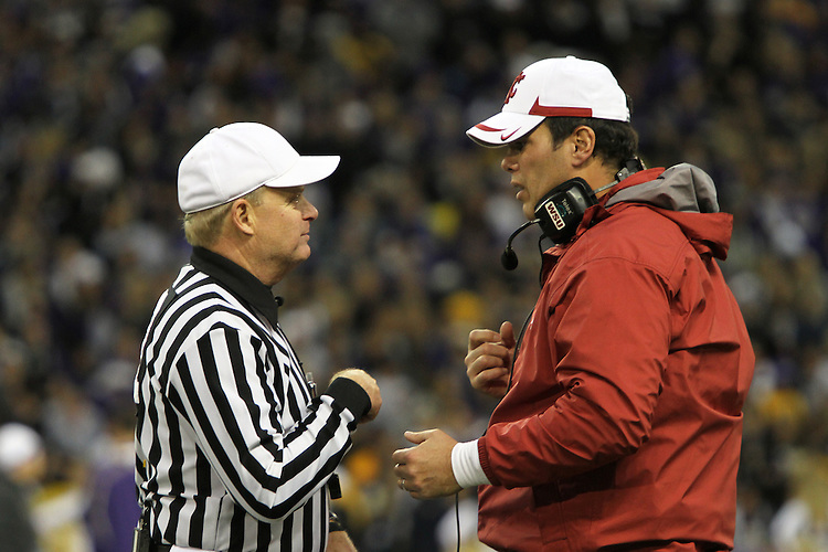 "Paul Wulff, Washington State head football coach, has a ""discussion"" with the head referee during the Cougars Pac-10 conference ""Apple Cup"" showdown with arch-rival Washington at Husky Stadium in Seattle, Washington, on November 28, 2009.  The Cougars lost to the Huskies in the game, 30-0."