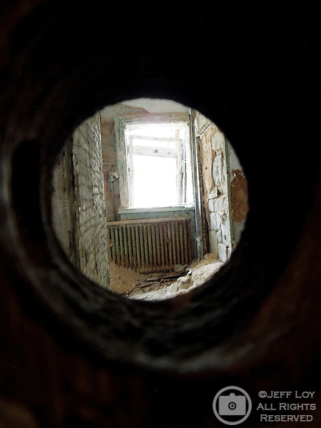 Looking throgh a key hole into an abandoned office at Eastern State Penitentiary in Philadelphia, Pennsylvania. The site is considered to be the world's first true penitentiary and when it opened in 1829, inmates were kept in complete solitary confinement. The penitentiary was closed in 1971 and is now a historical site and tourist attraction.