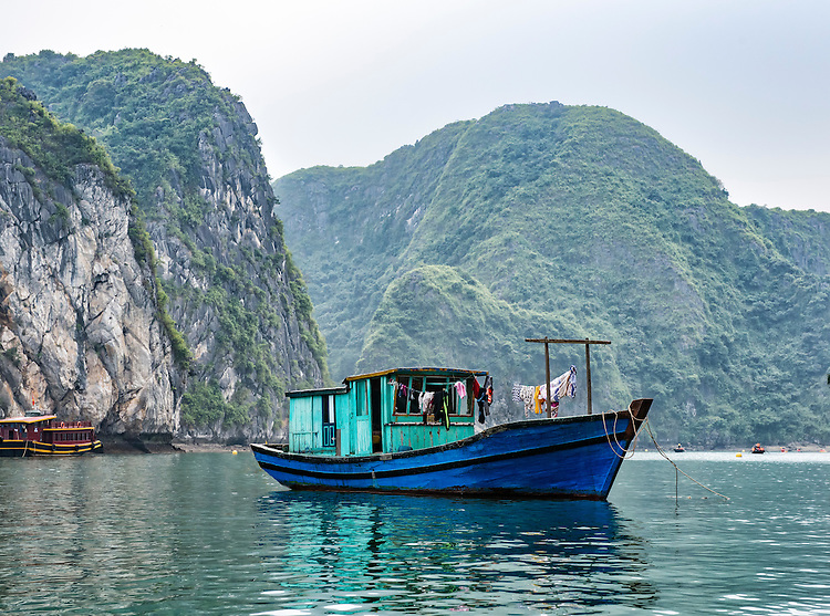 """A fishing boat moored in Ha Long Bay. Ha Long Bay, located on the east coast of Vietnam near Haiphong, contains over 1,900 limestone """"karst"""" islands projecting from the sea, frequently shrouded in fog, mist and rain."""
