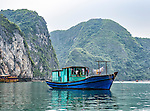 "A fishing boat moored in Ha Long Bay. Ha Long Bay, located on the east coast of Vietnam near Haiphong, contains over 1,900 limestone ""karst"" islands projecting from the sea, frequently shrouded in fog, mist and rain."