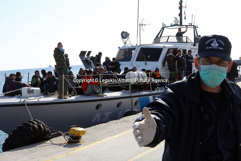 Pictured: A Coastguard officer asks people to move over as the vessel carrying some of the illegal immigrants docks to Ierapetra Thursday 27 November 2014<br />