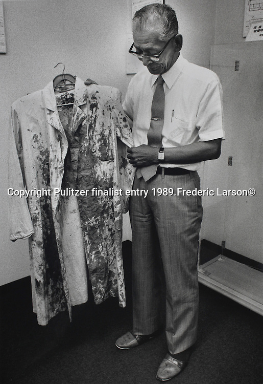 A doctor holds up a lab coat he wore at the time of the A-bomb explosion while treating patients in Hiroshima. .Pulitzer finalist entry 1989 Frederic Larson©