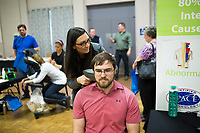 NWA Democrat-Gazette/CHARLIE KAIJO Nicci Brose, chiropractic assistant of Arbor Vitae Chiropractic, conducts a thermography scan on Taylor Stevens of Bella Vista (center), Thursday, March 15, 2018 at Riordan Hall in Bella Vista. <br />