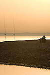 Fisherman relaxing in beach chair at dusk while watching his rods