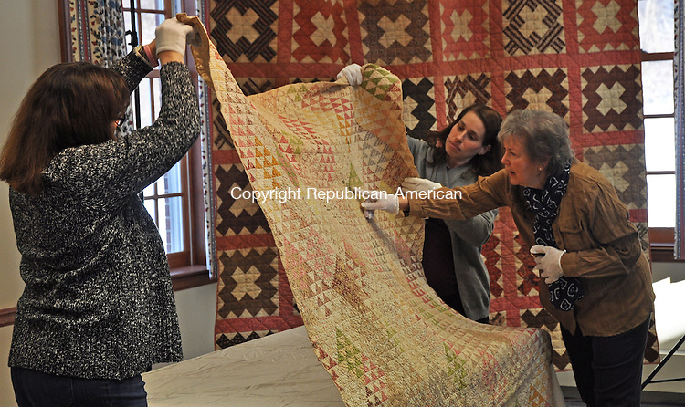 KENT, CT – 14 January 2014 - 011414LMW01 – Quilt expert Sue Reich of Washington points out a detail in one of several antique quilts owned by the Kent Historical Society that were examined and shared with the public during a program 'Learning History From Quilts' Sunday at Kent Town Hall. The quilt is held up by Lyn Stirnweiss and Melissa Cherniske, who are both members of the society's Programs Committee. A total of 64 people attended the event. CONTRIBUTED