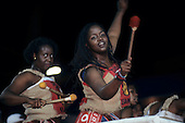 Bahia State, Brazil. Carnival; Dida girl drummers with large beaters wearing sacking costumes.