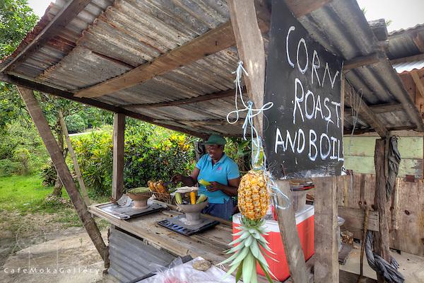 Smiling woman vendor selling corn  on the roadside