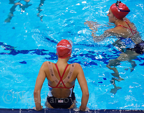 26 JUL 2012 - LONDON, GBR - Synchronised Swimmer Asha Randall (GBR) of Great Britain lowers herself into the water during practice at the Aquatics Centre in the Olympic Park, Stratford, London, Great Britain ahead of the start of the London 2012 Olympic Games .(PHOTO (C) 2012 NIGEL FARROW)